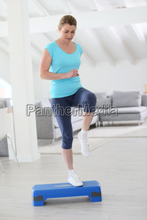 middle aged woman doing step exercices