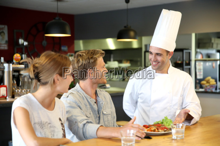 young chef serving cooked dish to
