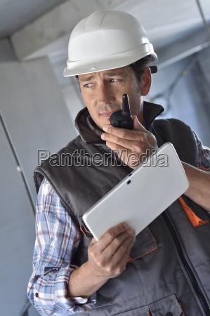 entrepreneur on building site using walkie