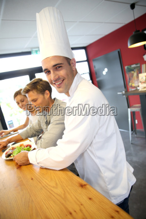 smiling chef serving customers in restaurant