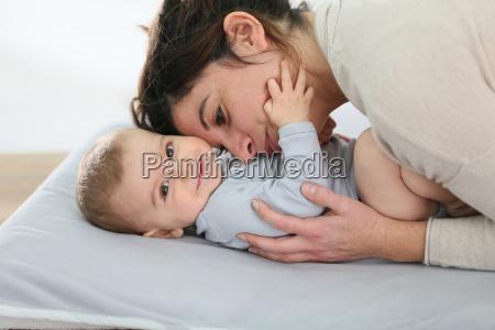 mommy cuddling baby boy on changing