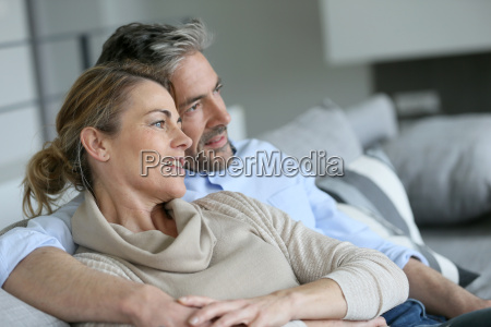 mature couple sitting in sofa looking