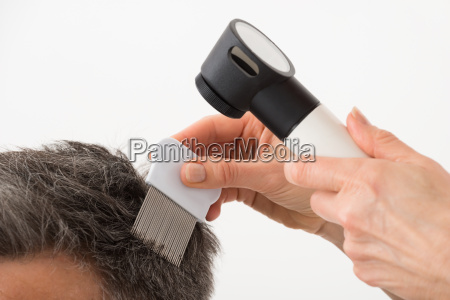 person with dermatoscope examining patients hair