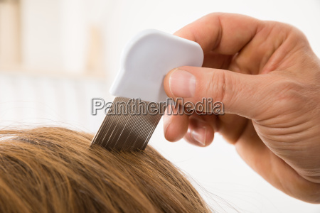 person using lice comb on patients