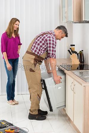 male worker repairing oven