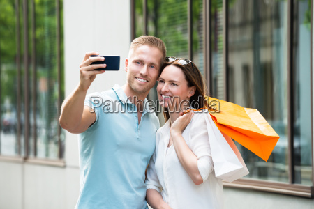 couple with shopping bag taking picture