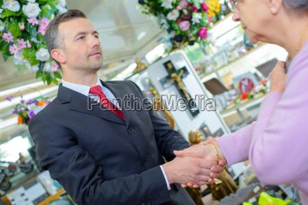 funeral director shaking hands with elderly