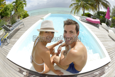 cheerful couple sitting by swimming pool