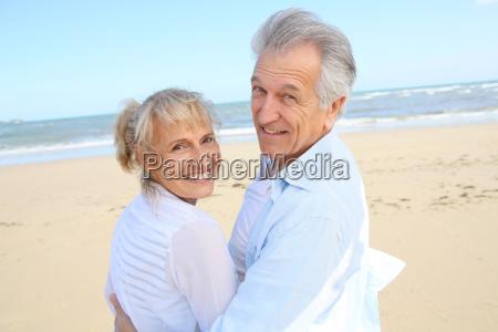 munter senior par staende pa stranden