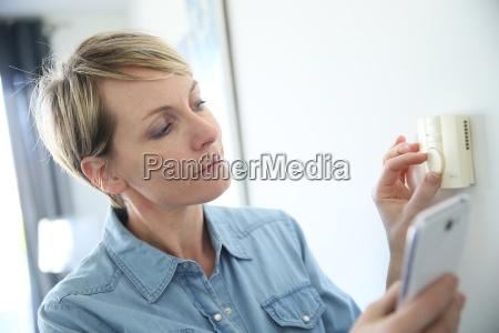 woman porgramming indoor temperature with smartphone