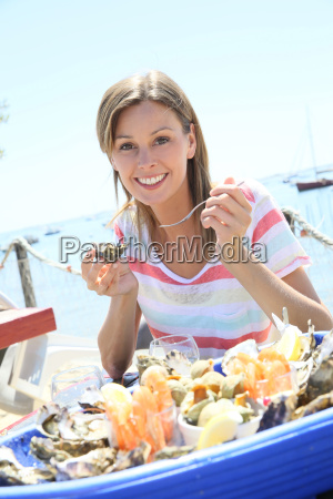 cheerful woman tasting fresh oysters by