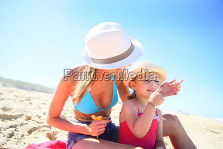 woman applying sunscreen on daughters body