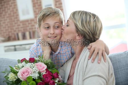 woman kissing little boy on mothers