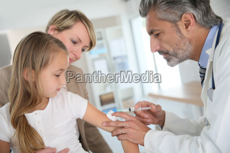 young girl receiving vaccination in doctors