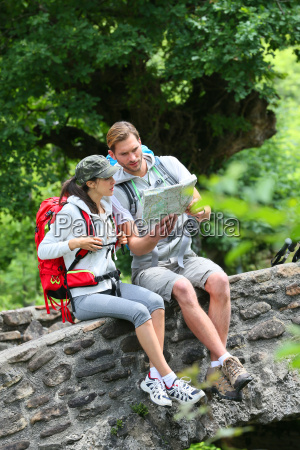 couple of hikers reading map on