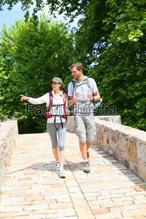 couple with backpack walking on stone