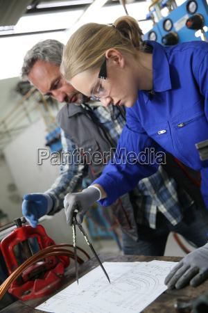apprentice in plumbing using compas to