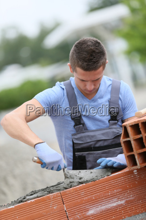 young brick layer working outside on