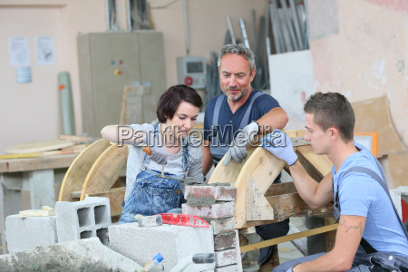 instructor teaching teenagers brick laying
