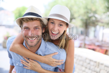 cheerful man giving piggyback ride to