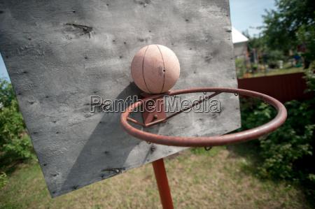 old basketball and basket on weathered
