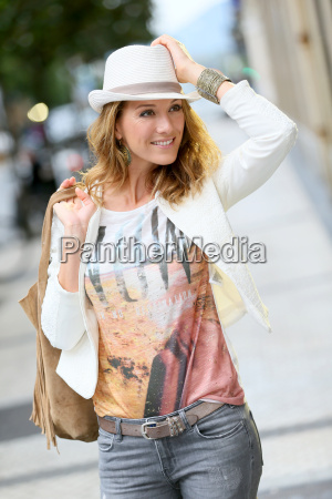 trendy woman with hat walking in