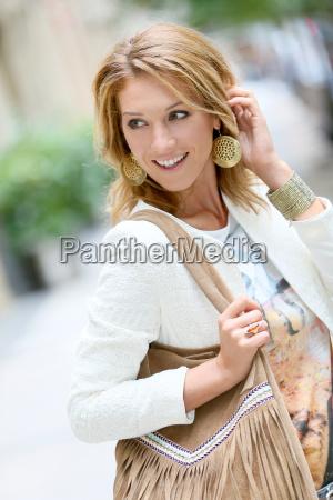 attractive trendy woman walking in city