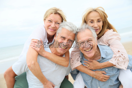 senior men giving piggyback ride to