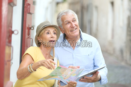 senior tourists walking in street with