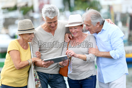 senior tourists using tablet on visiting