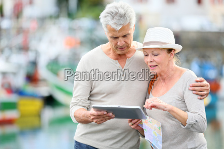 senior couple looking at map while