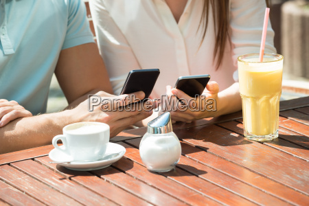 couple sitting on bench using mobile