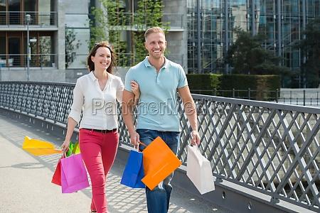 couple walking on bridge with shopping