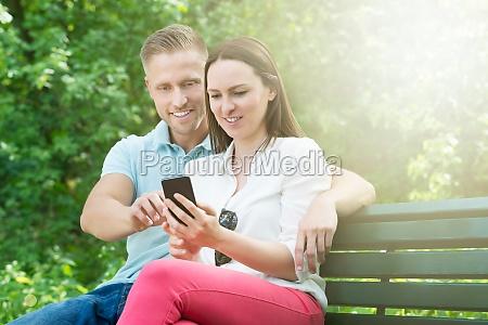 couple using mobile phone in garden