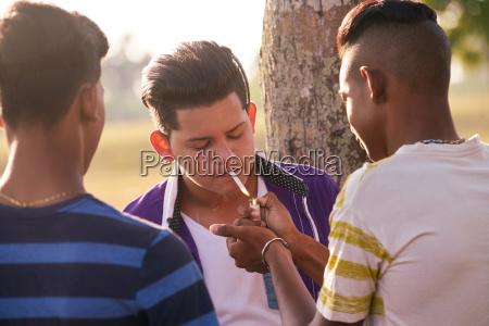 group of teenagers boy smoking cigarette