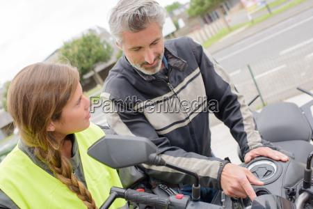 instructor explaining motorcycle to lady
