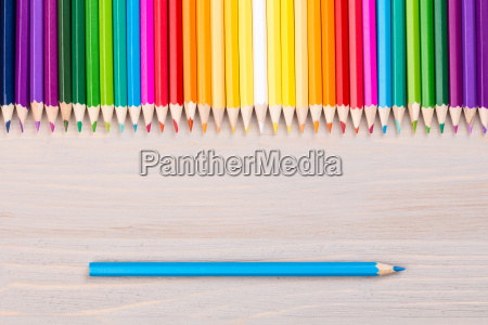 color pencils on wooden background with