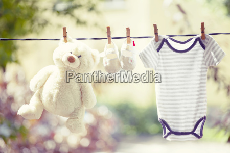 baby clothes boots and teddy hanging
