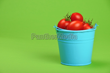 blue bucket of red cherry tomatoes