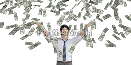 asian man catching money falling from