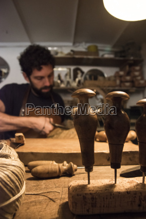 artisan braiding a wicker bulls head