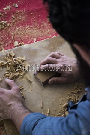 hands of carpenter sanding a wood