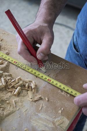 hands of a carpenter measuring a