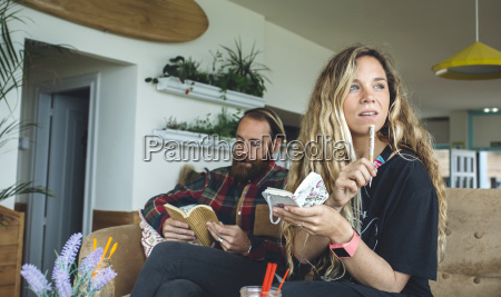 couple sitting in cafe woman writing