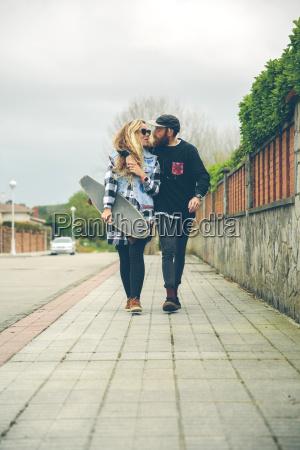 couple in love with skateboard walking