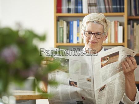 portrait of senior woman reading newspaper
