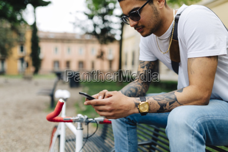 young man sitting on bench looking