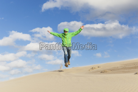 enthusiastic mature man jumping over sand
