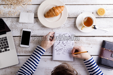 man working at table with croissant