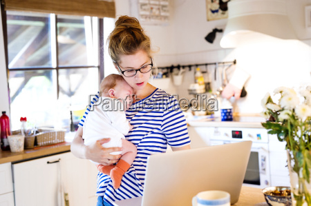 mother with baby in kitchen looking
